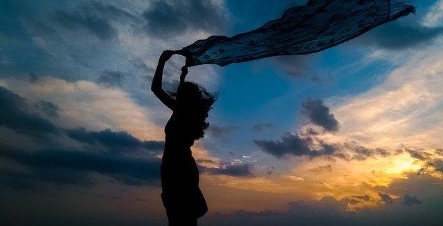 Silhueta de mulher com canga ao vento com céu com nuvens ao fundo