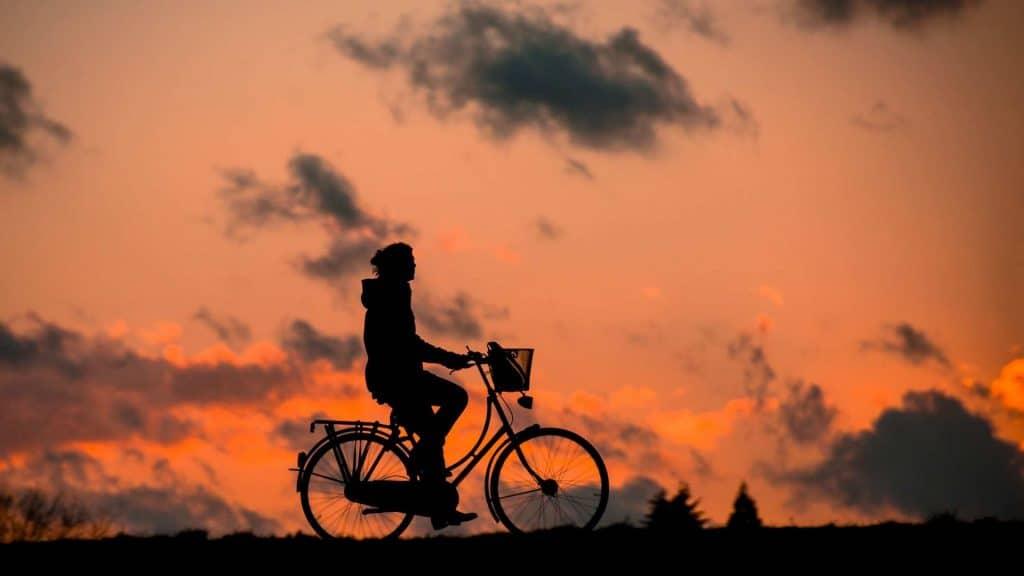Homem sobre uma bicicleta. Ao fundo por do sol.