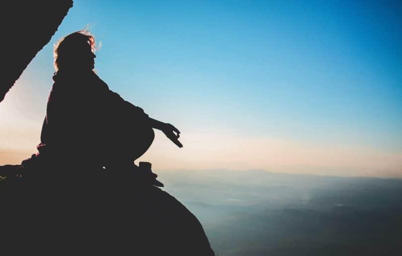 Silhueta de pessoa meditando em pedra com céu ao fundo