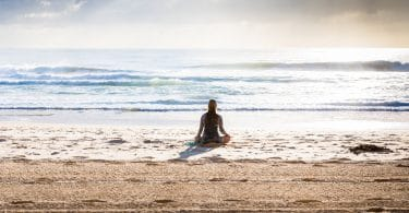 Mulher meditando na praia.