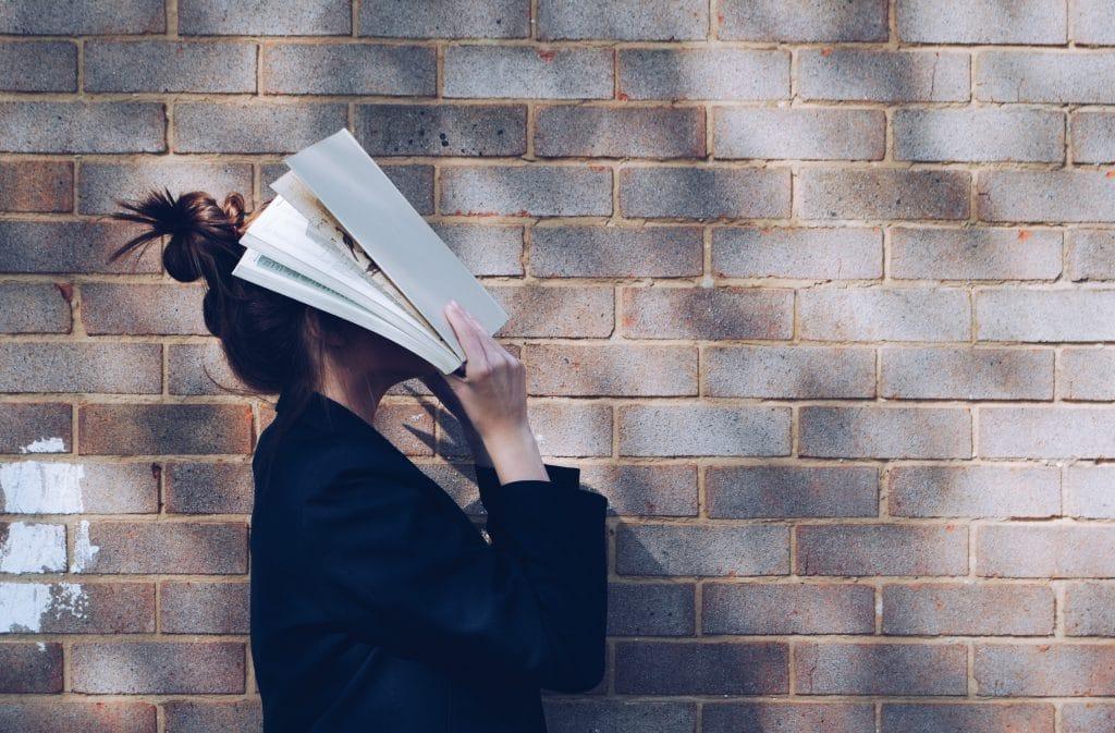 Mulher com o livro no rosto