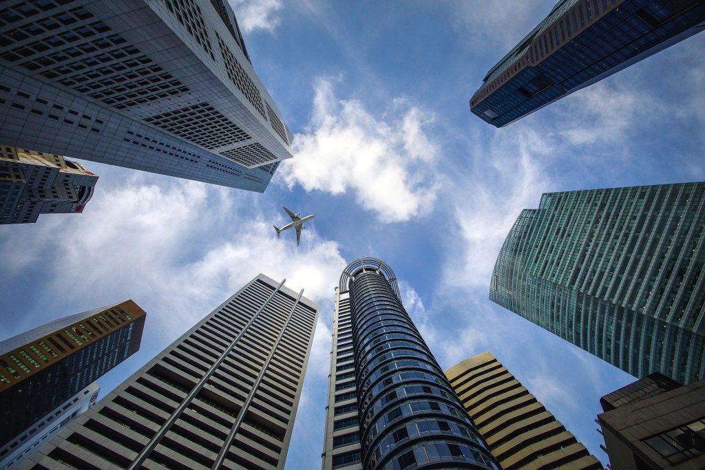 Um avião no centro de um arranha céu - prédios bem altos em uma cidade oriental.