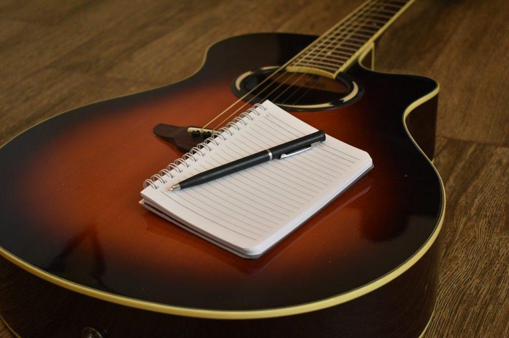Caderno e caneta sobre um violão.