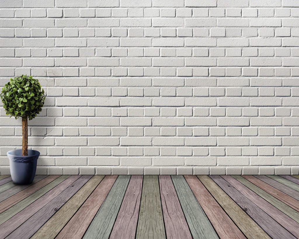 Parede de um quarto pintada na cor branca. Ao lado um vaso cinza com um arranjo. O piso do quarto é de madeira colorido.
