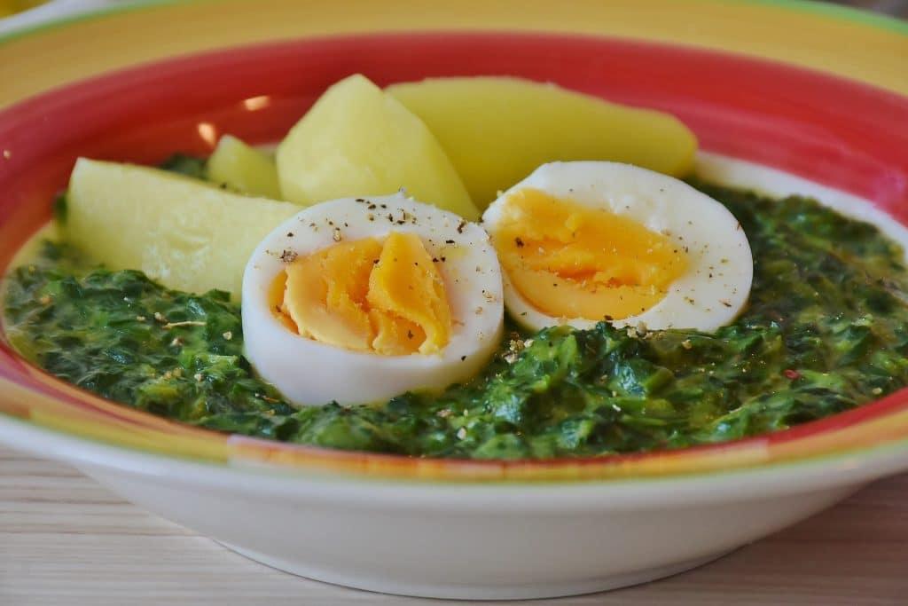 Sopa de espinafre servida com ovos e batatas cozidas.