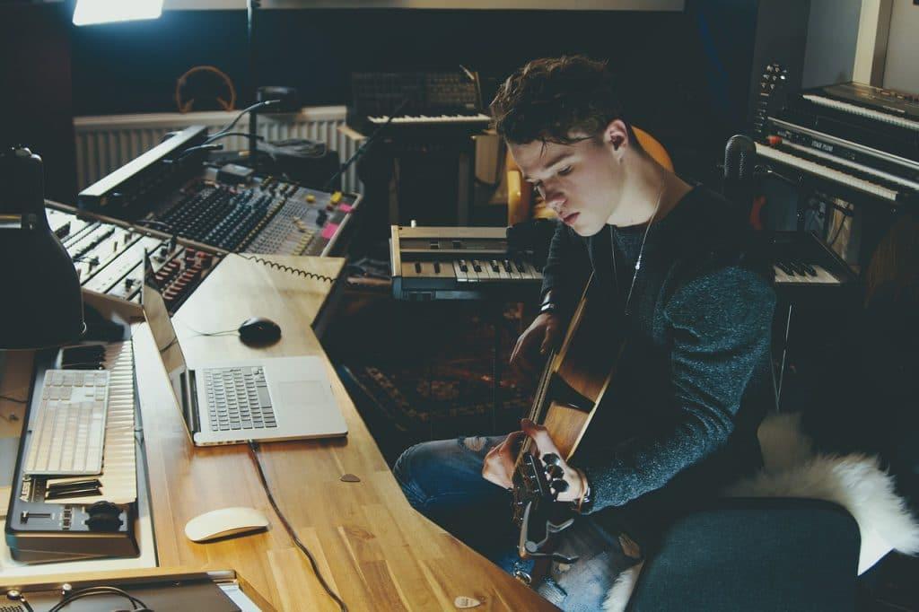 Homem sentado em um estúdio musical com computadores e equipamentos de som, tocando um violão.