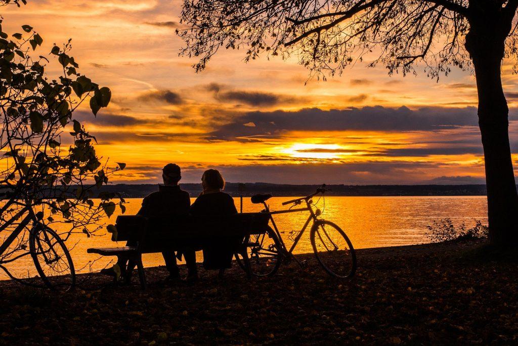 Imagem de um casal de homem e mulher sentados em um banco de frente para um lago assistindo o por do sol. Ao lado do banco, temos uma bicicleta e duas árvores, uma de cada lado.