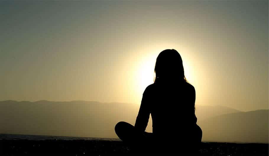 Silhueta de mulher de costas, sentada com as pernas cruzadas, durante o pôr do sol.