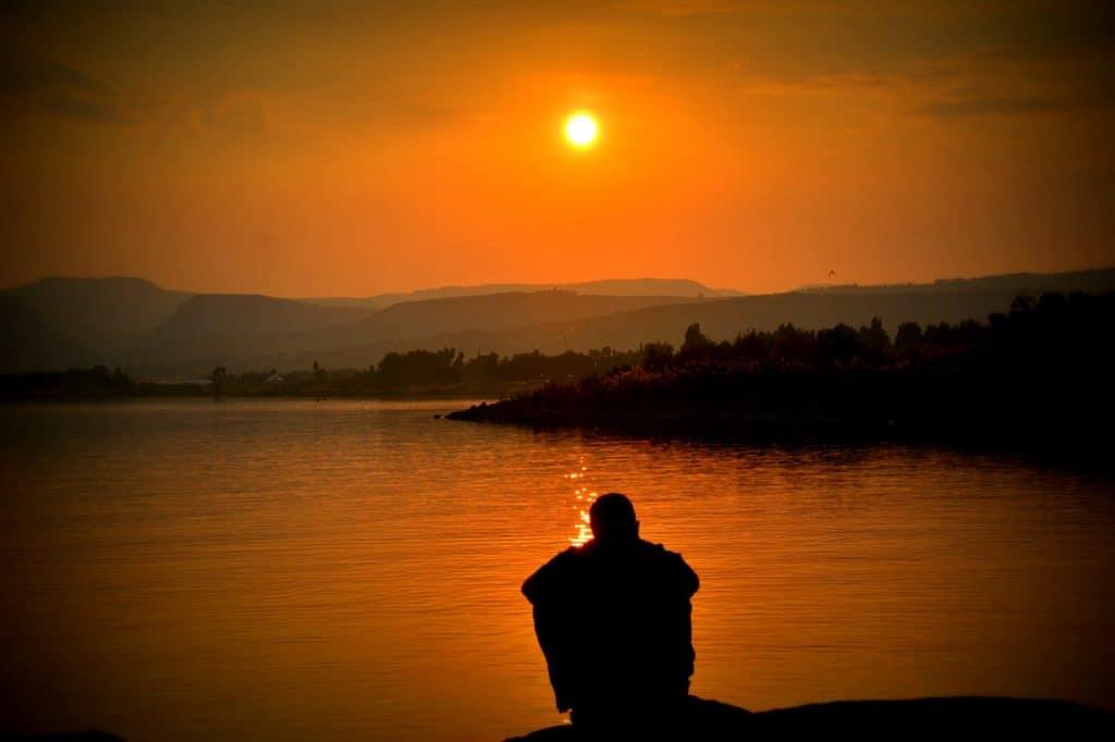Silhueta de pessoa sentada a beira de um lago, abraçando suas pernas. O céu está laranja como em um fim de tarde mas o sol ainda brilha.