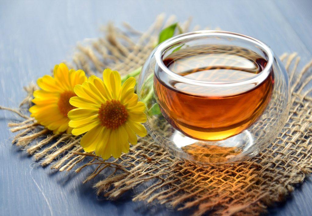 Chá de açafrão servido em uma caneca de vidro. Ela está sobre um tecido de juta e ao lado duas margaridas amarelas enfeitam a juta.