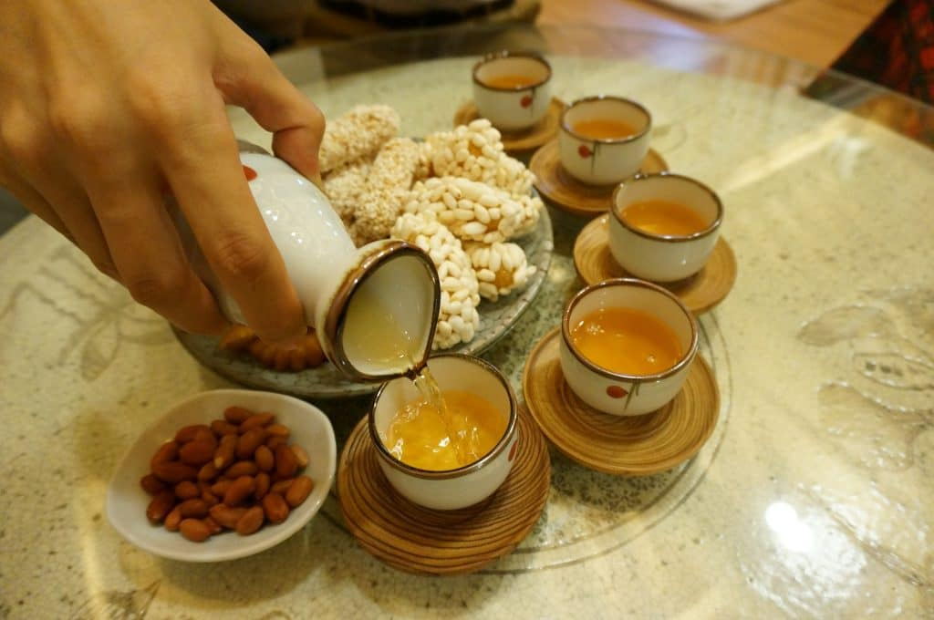Mão de uma mullher segurando um recipiente cheio de chá. Ela está servindo o chá em várias xícaras.