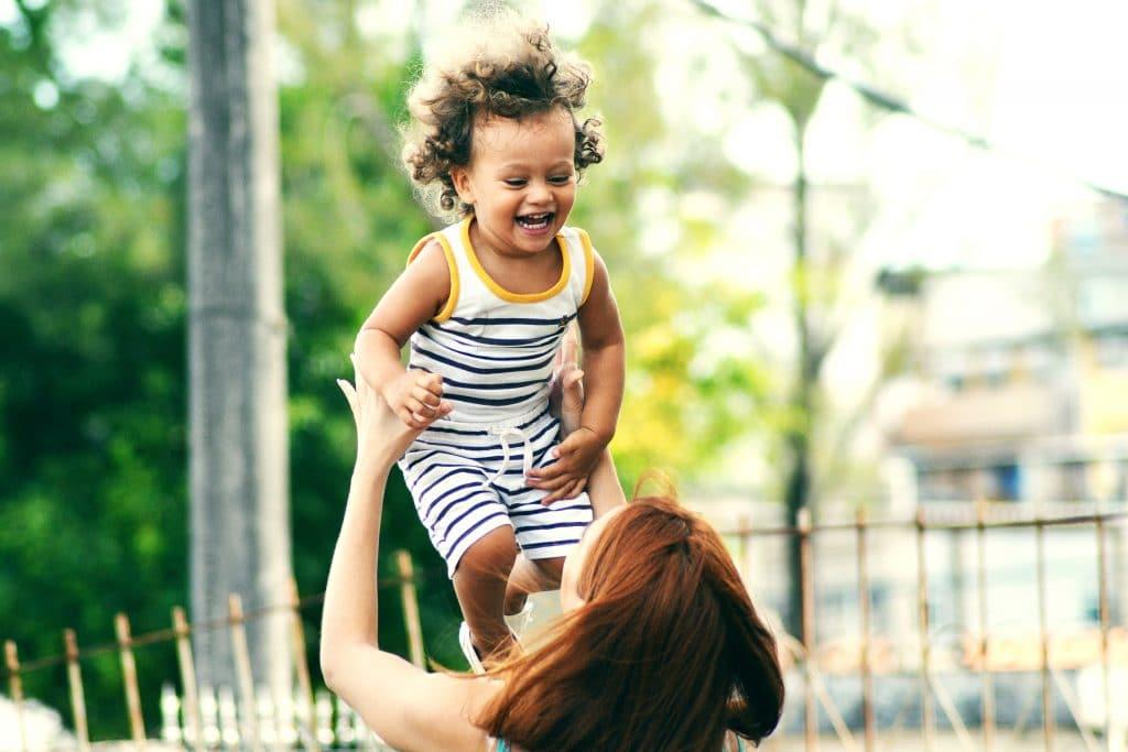 Mulher levantando criança sorrindo no ar.