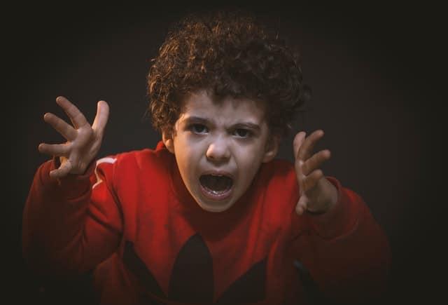 Menino irritado gritando com mãos para o alto