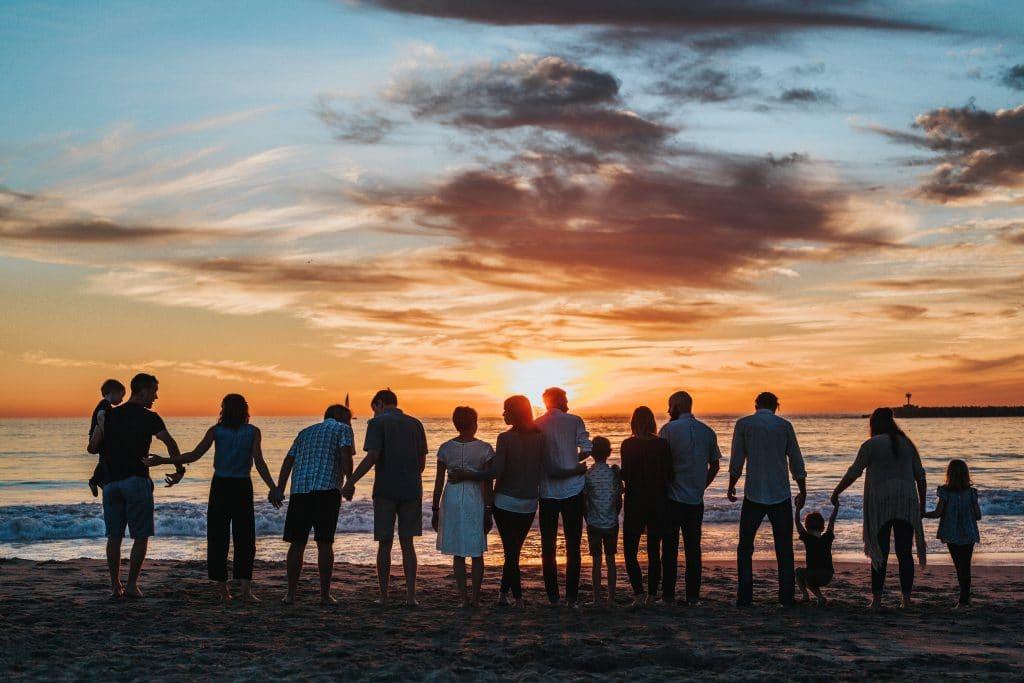 Foto de diversas pessoas na praia de mãos dadas. Ao fundo há um pôr-do-sol.
