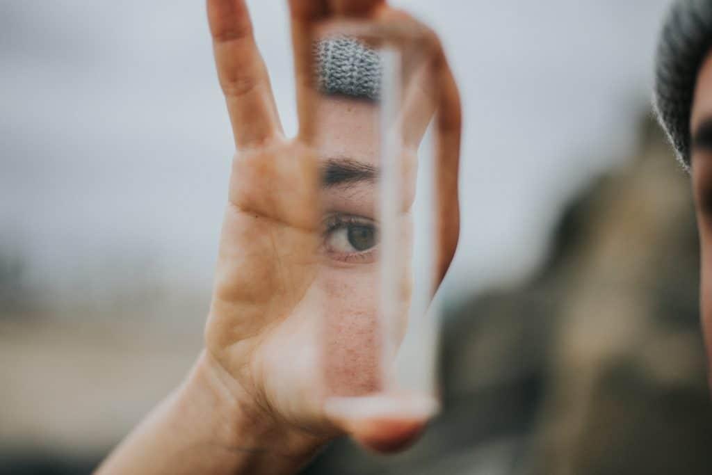 Homem de touca olha seu próprio reflexo por meio de um pedaço de espelho comprido.