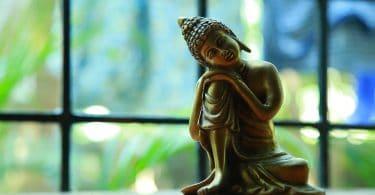 Imagem de Buda reflexivo em mesa com janela ao fundo