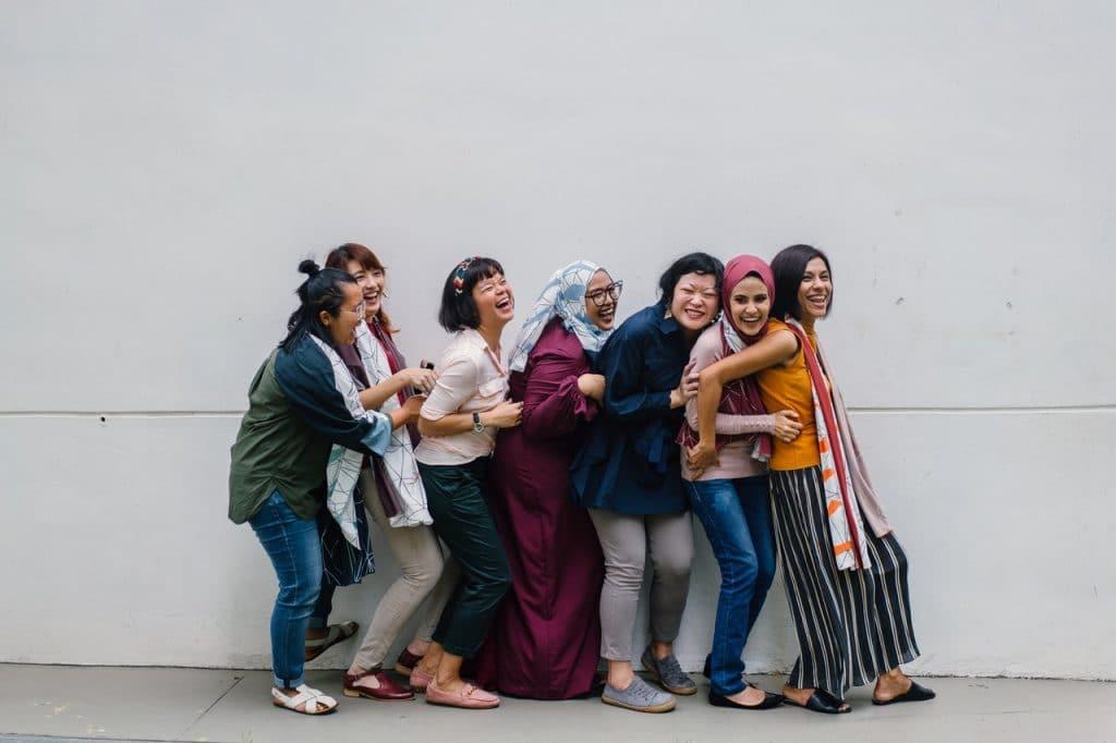 Mulheres de diversas religiões, culturas e etnias rindo juntas enquanto formam uma fila.