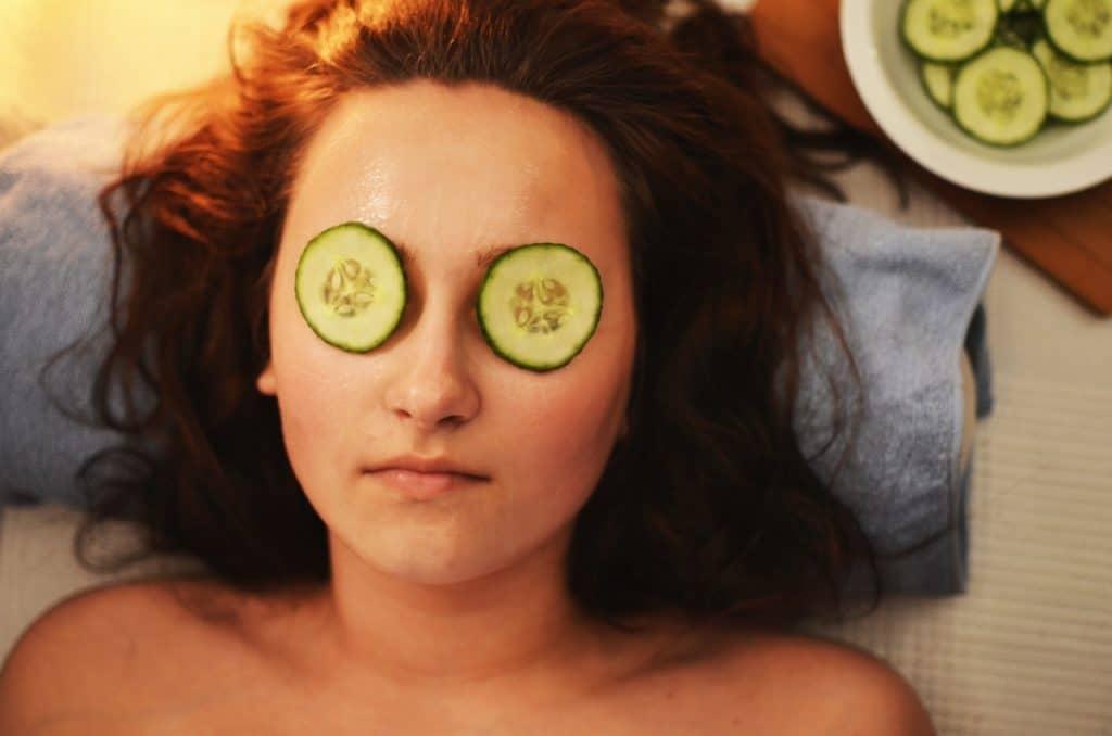 Mulher deitada com a cabeça sobre uma toalha e rodelas de pepinos nos olhos.