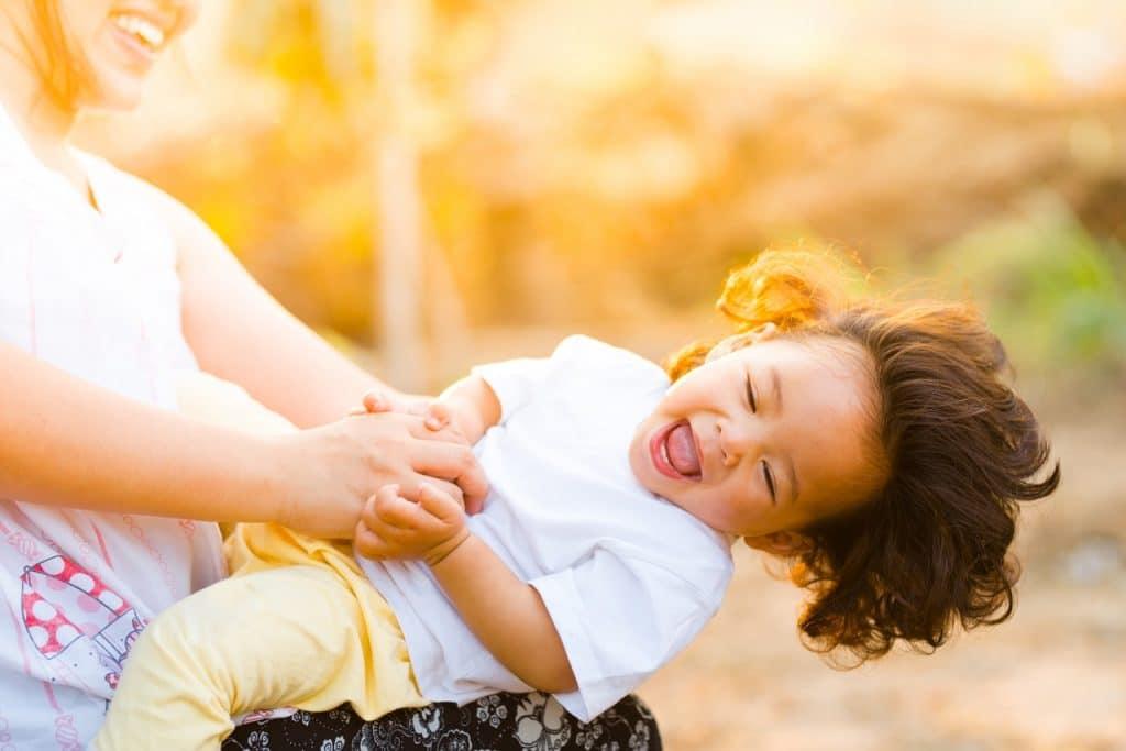 Criança brincando no colo da mãe, sorrindo e com os cabelos ao vente, em um parque ao pôr do sol.
