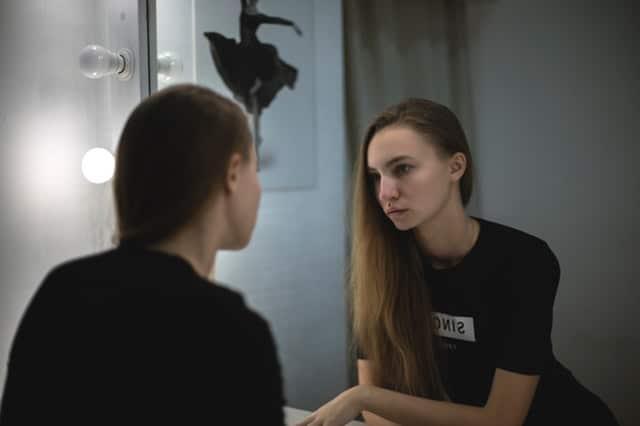 Garota se olhando no espelho com luz de camarim
