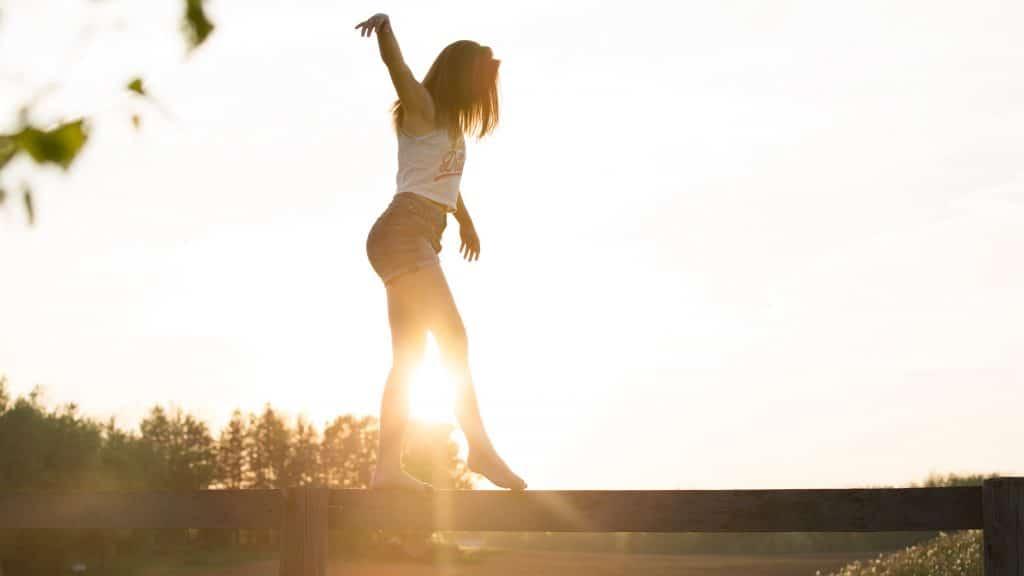 Mulher equilibrando-se em ponte de madeira com sol refletindo ao fundo