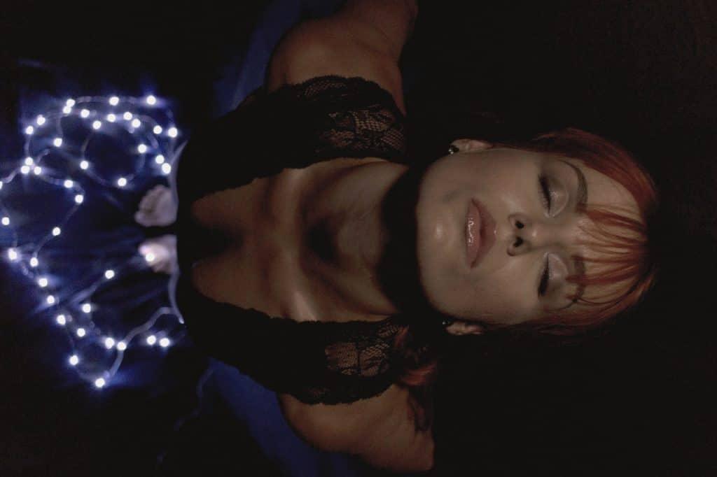 Mulher com os braços abertos, com a cabeça inclinada para trás, e os olhos fechados. Ela pisa em fios de luz.