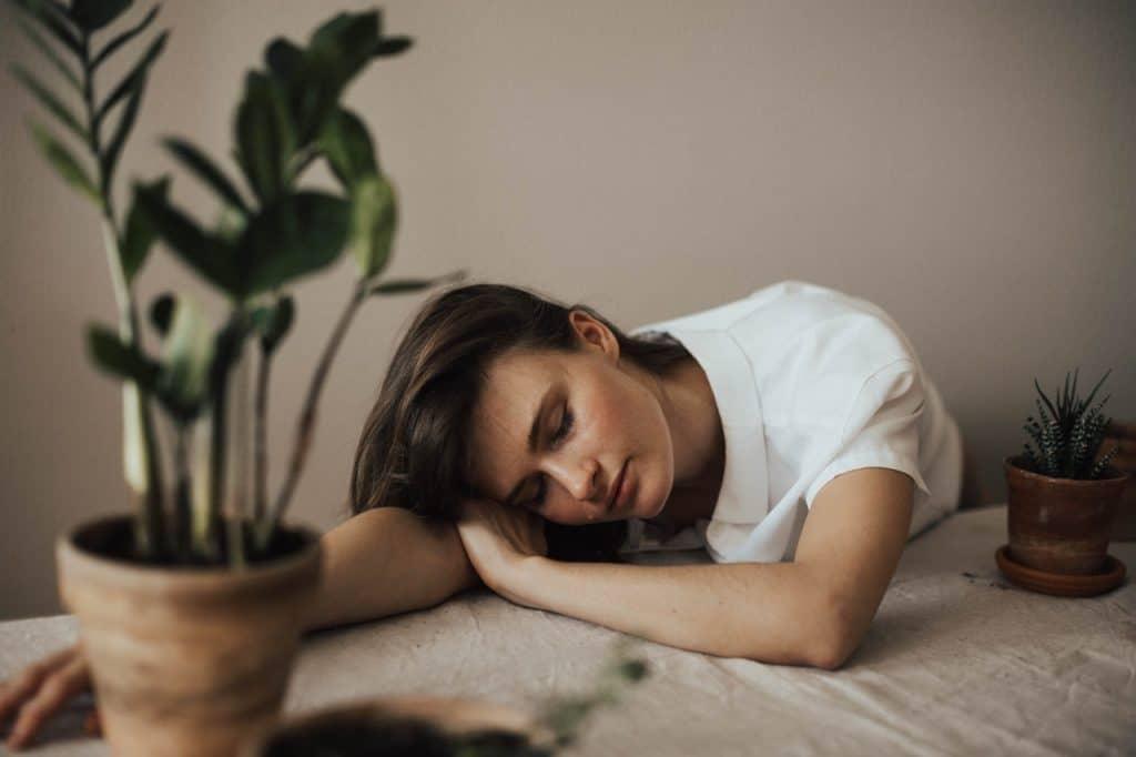 Mulher dormindo em cima de uma mesa, com a cabeça apoiada sobre o braço e cercada por vasos de plantas.