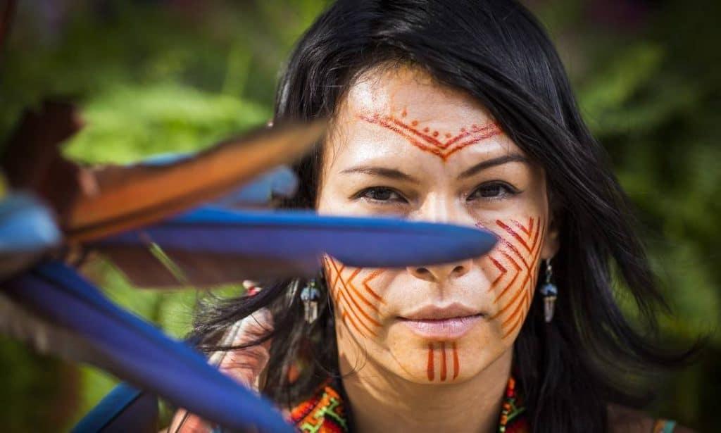 Fotografia de Daiara Tukano, com pinturas tradicionais no rosto, em meio a uma floresta.