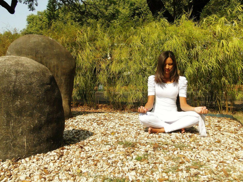 Mulher vestida de branco sentada em posição de meditação. Ela está no meio da natureza. Ao fundo muitas árvores e ao lado pedras grandes.