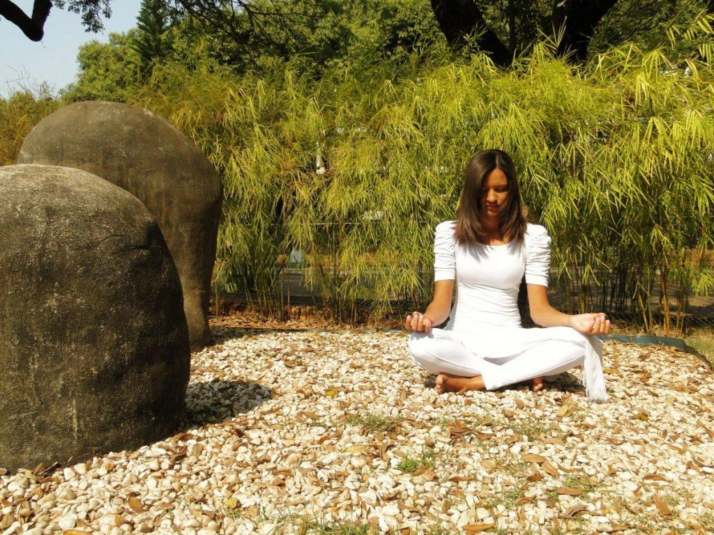 Mulher sentada com as pernas cruzadas em jardim com pequenas pedras brancas e folhas secas. Ela está meditando, e ao fundo muitos bambus plantados e árvores maiores.