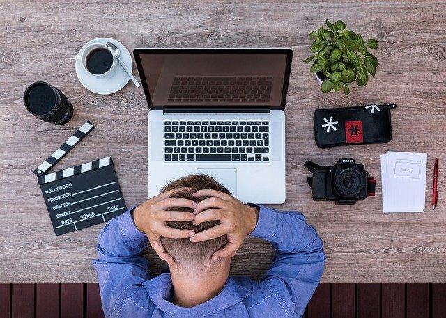 Homem em mesa de trabalho cansado visto do alto