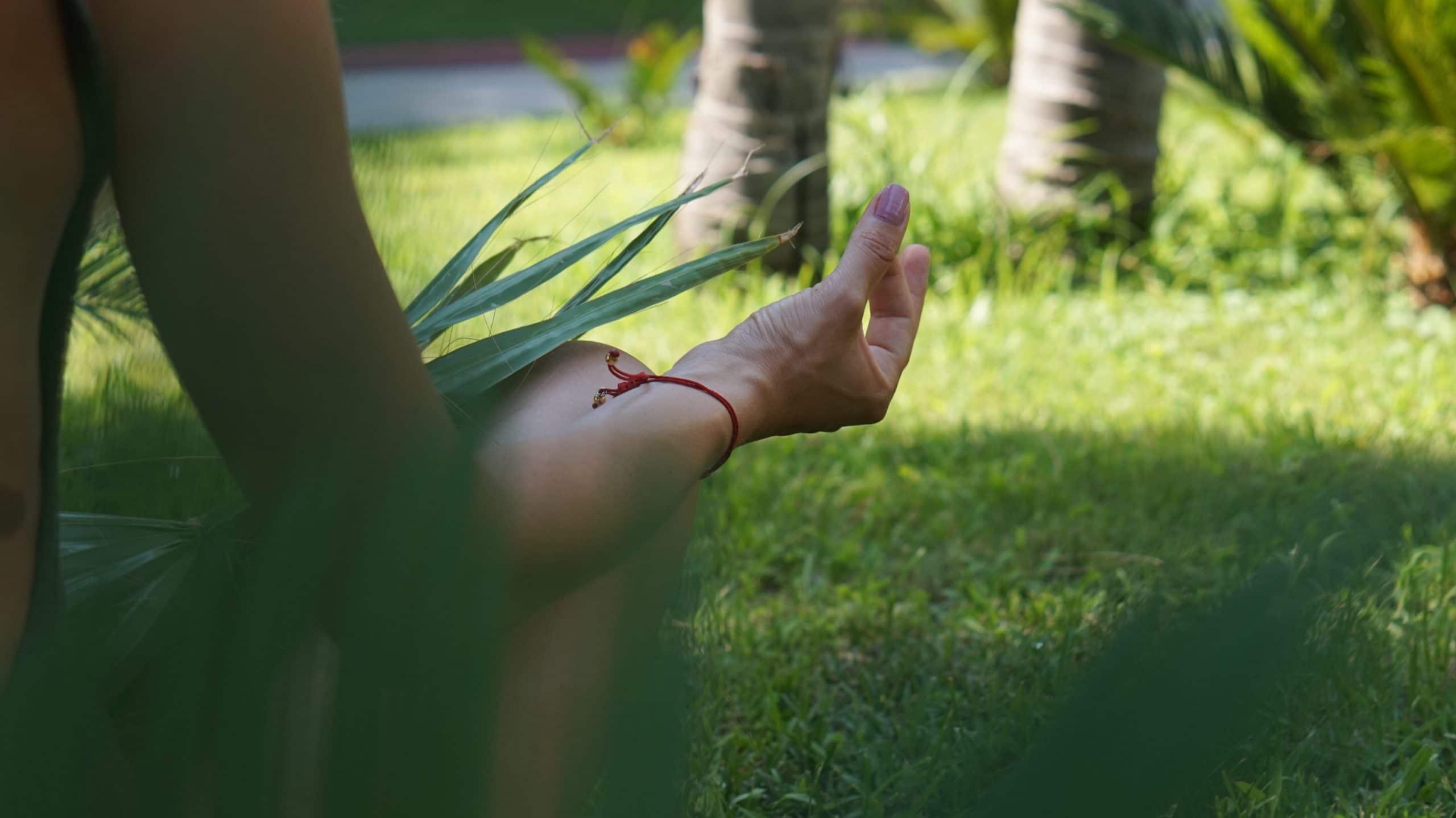 Mulher sentada em um gramado fazendo meditação