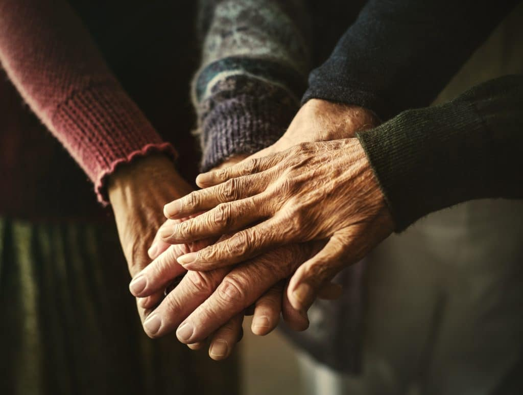 Imagem de várias mãos de pessoas idosas, umas sobre as outras. Trazendo um sentimento de compaixão e simpatia.
