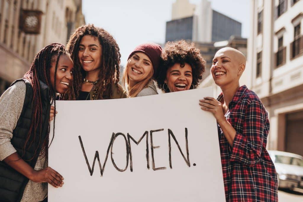 """Mulheres em um protesto de empoderamento feminino segurando cartaz escrito em inglês """"mulheres"""""""