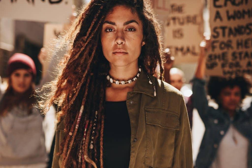 Mulher em frente a um protesto de empoderamento feminino