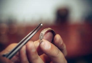 Ourives colocando um diamante em um anel com uma pinça.