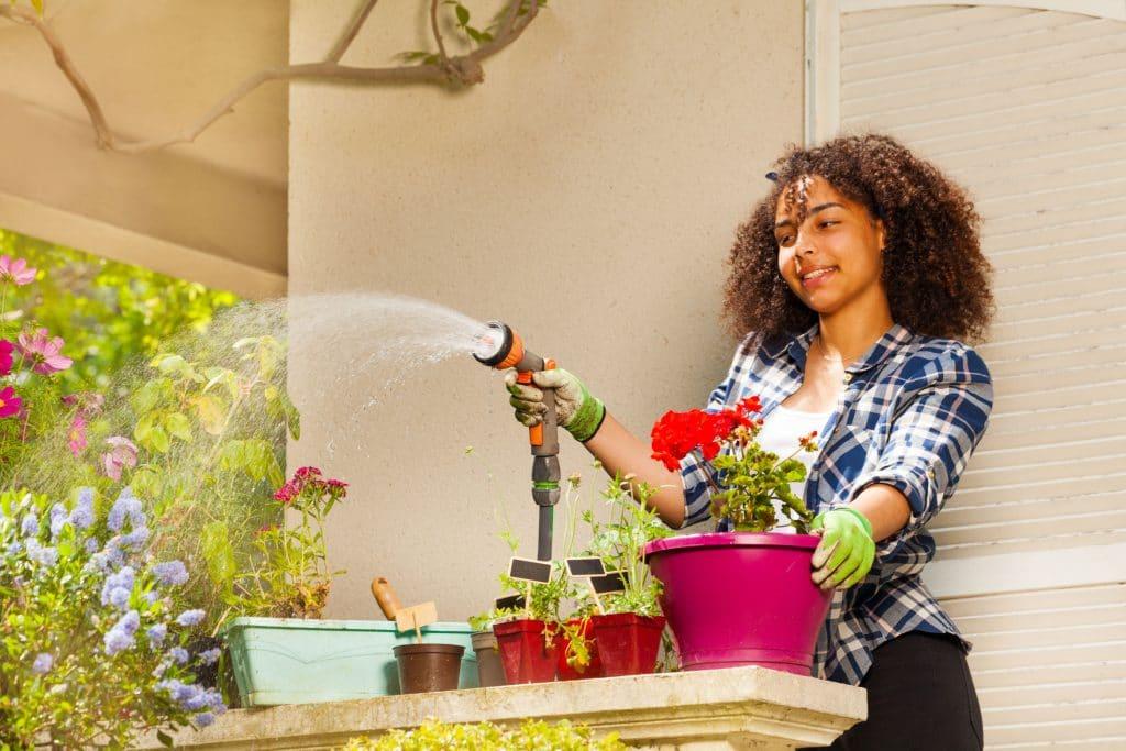 Mulher regando vasos de plantas.