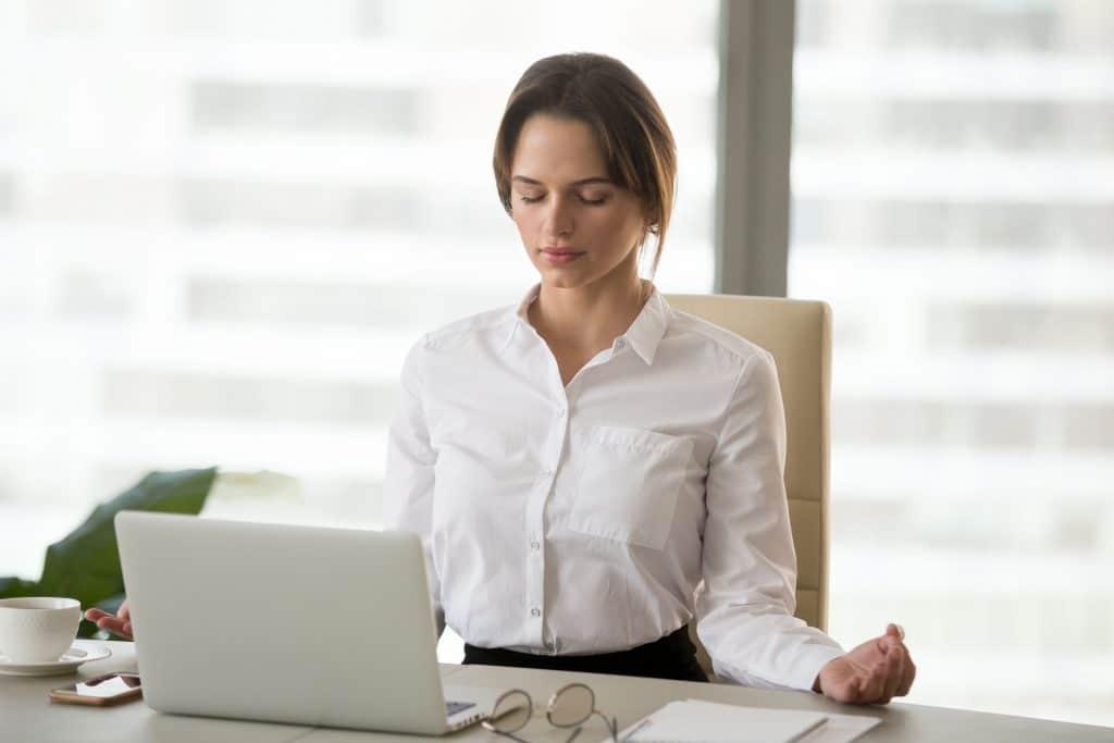Mulher em escritório sentada em frente a um notebook, com os olhos fechados e meditando.