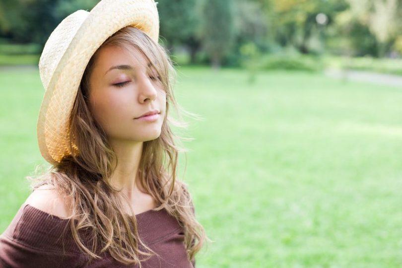 Garota de olhos fechados e chapéu com fundo de grama e árvores