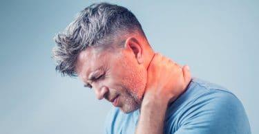 Homem com a mão no pescoço com expressão de dor