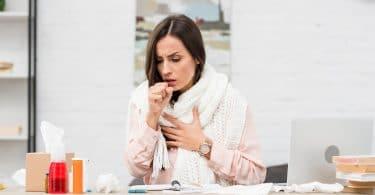 Mulher usando blusa de mangas compridas e cachecol, com uma mão no peito e a outra em frente de sua boca. Em sua frente, em uma mesa, vários lenços de papel amassados, e embalagens de medicamentos.