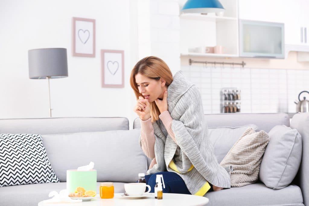 Mulher sentada em seu sofá cinza claro. Ela está com gripe e tossindo muito. Em frente ao sofá temos uma mesinha de centro branca e sobre ela vários medicamentos para a gripe e chás feitos com laranja e mel.