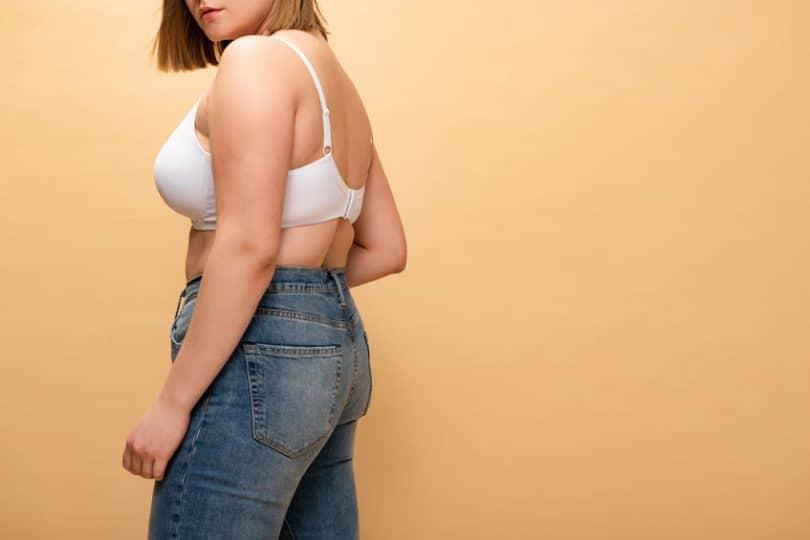 Mulher com top e calça jeans e olhando de costas