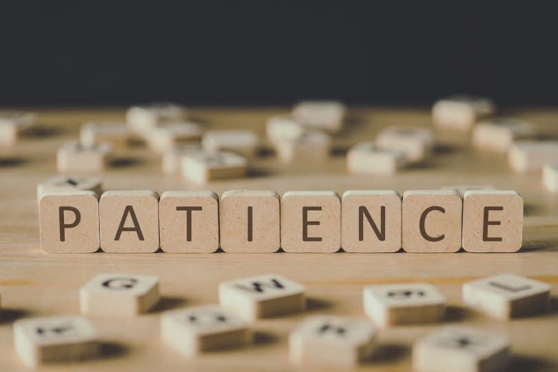 """Blocos de madeira formando a palavra """"patience""""."""