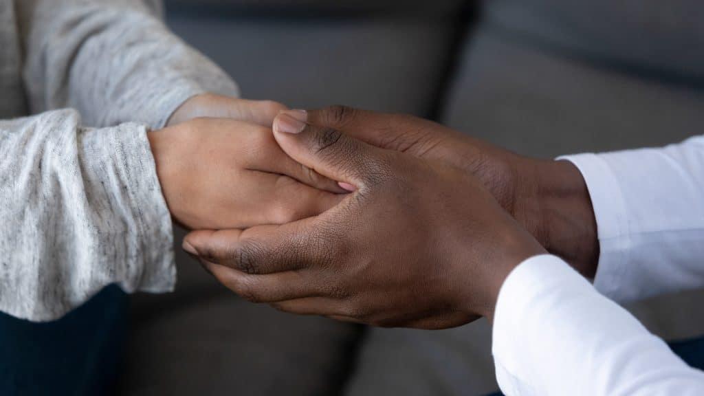 Imagem de uma mão de um homem negro segurando nas mãos de uma criança branca, demonstrando respeito e empatia.