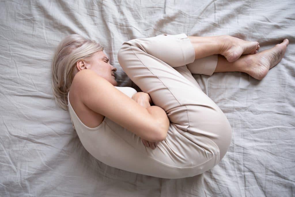 Mulher deitada sobre a sua cama se contorcendo com fortes dores no estômago.