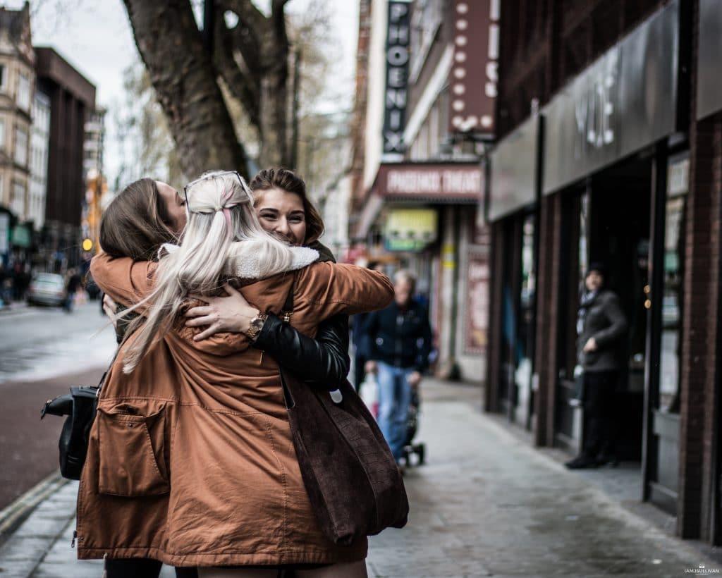 Três mulheres se abraçando na calçada