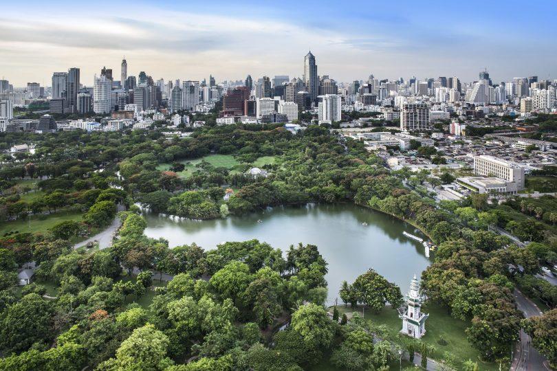 Lago cercado por vegetação, e uma cidade grande com muitos prédios ao fundo.