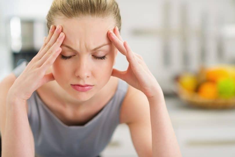 Mulher apoiada com seus cotovelos em uma bancada, olhos fechados e os dedos apoiados na testa.