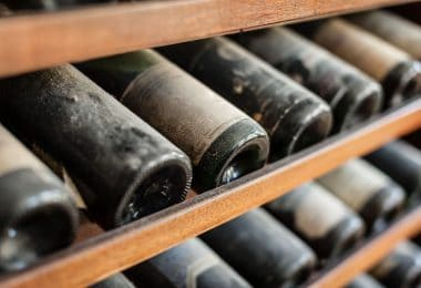 Garrafas de vinho envelhecidas enfileiradas em uma adega.